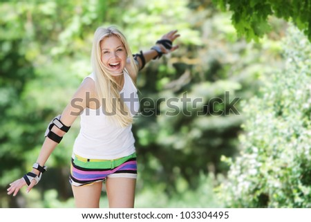 Rollerblade / roller skating woman going skating on inline roller blades. Young happy girl enjoying outdoor workout