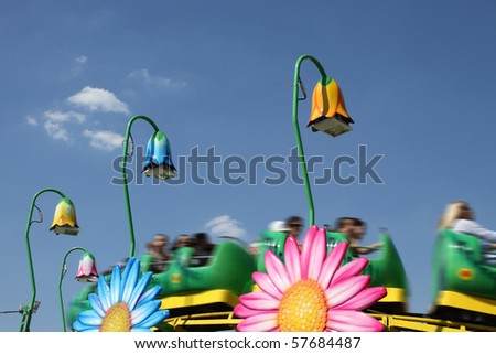 rollercoaster for childrens in an amusement park against blue sky