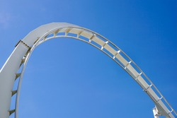 Rollercoaster track against a brilliant blue sky