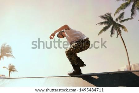 Rollerskater man is performing tricks in skatepark on sunset. #1495484711