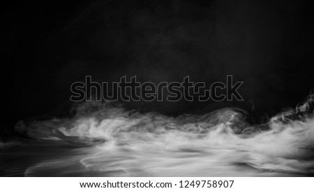 Rolling billows of smoke mist clouds from dry ice across the bottom light . Fog on floor isolated background  black texture .