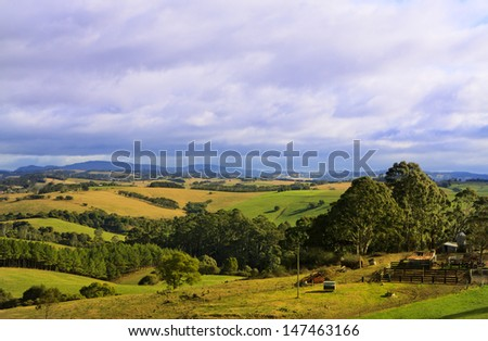 Rolling farmland hills under an overcast cloudy sky