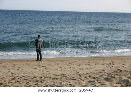 Rolling ocean picture with a man standing looking out at the waves.