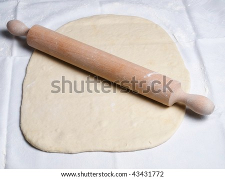 Rolling pin and dough during food preparation.