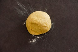 rolling pin and dough on a dark table with flour, homemade cakes, low key. food preparation. Dark rustic style.
