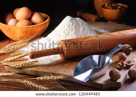 Rolling pin and flour on an old wooden desk in a rustic kitchen