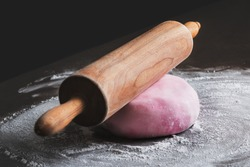 Rolling pin and pink sugar paste on kitchen counter. DIY, sequence, step by step.