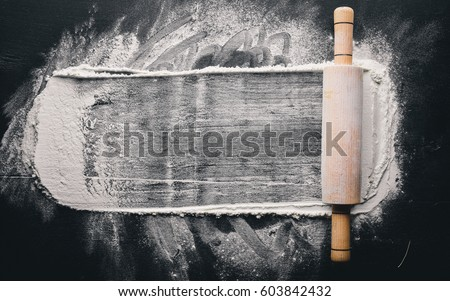 Rolling pin and white flour on a dark background. Free space for text . Top view. #603842432