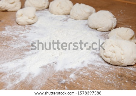 Rolling pin, dough and flour on the table. The process of making homemade cakes. Homemade baking. Cooking from home dough.