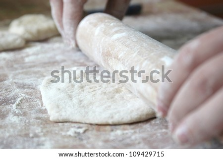 Rolling pin in hands on the wooden table