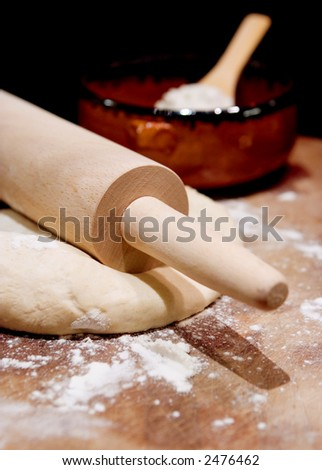 Rolling pin on dough with scattered flour and bowl of flour in background.