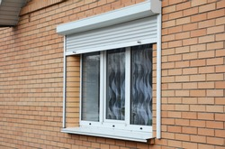Rolling shutters brick house windows protection. Brick house with metal roller shutters on the windows