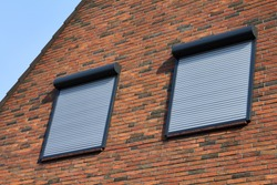 Rolling shutters brick house windows protection. Brick house with metal roller shutters on the windows.