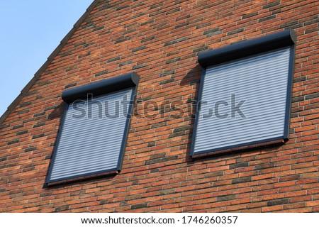 Rolling shutters brick house windows protection. Brick house with metal roller shutters on the windows. Stock photo ©