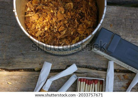 Rolling tobacco in a round box next to the cigarette rolling machine, tubes and a matchbox. Tobacco health risks concept, Foto d'archivio ©