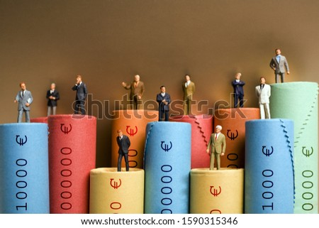 Rolls of assorted Euro coins with businessmen figurines