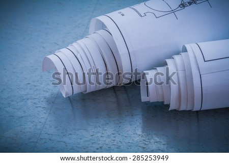 Rolls of blueprints on metallic background building and architecture concept
