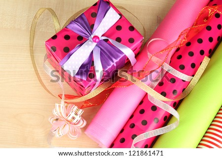 Rolls of Christmas wrapping paper with ribbons, bows on wooden background