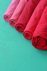 Rolls of clothes and fabrics of red and pink colors lie in a row diagonally on a green table background