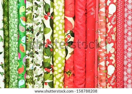 Rolls of colorful christmas fabric as a vibrant background image