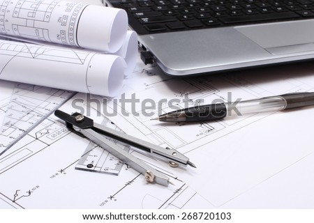 Rolls of electrical diagrams, construction drawings of house, accessories for drawing and laptop, drawings and accessories for the projects engineer jobs