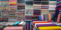 Rolls of fabric and textiles in a factory shop. Multi different colors and patterns on the market Fabrics in rolls. Fabric store in turkey