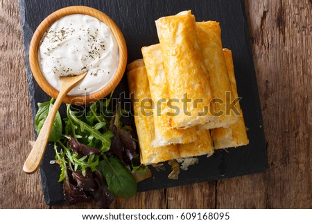 Rolls of filo stuffed with meat, eggs and greens close-up on the table. Horizontal view from above