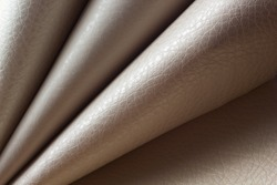 Rolls of genuine leather. Materials for the leather industry. Leather beige shades in rolls. Different skin samples. Beige, light brown natural leather.