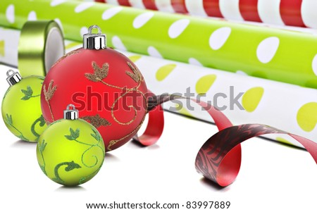 Rolls of gift wrapping paper and  ribbon  with red and green christmas baubles