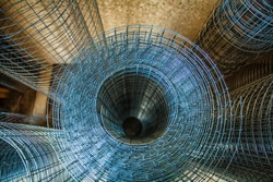 Rolls of iron mesh (wire mesh) use for reinforce concrete in construction site. Metal grid. Grid of pending orders. Metal mesh in rolls. Close-up.