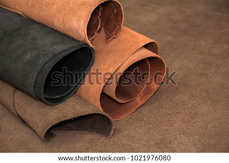 Rolls of natural brown and black leather. Materials for leather craft #1021976080