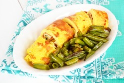 Rolls of omelette with cheese on a plate, fried green beans