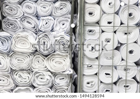 Rolls of white fabric Stored in warehouse, close up view, textile raw materials stock