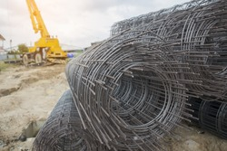 Rolls of wire mesh steel for construction put a pile on the ground, against mobile crane background. Steel wire bar in construction site.Steel reinforcement rod for concrete. Construction  concept.