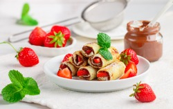 Rolls with chocolate and nut filling, fresh strawberry berries, powdered sugar and mint. Delicious gourmet Breakfast. Selective focus