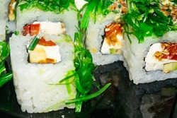 Rolls with fish, cheese and green algae. A traditional Japanese dish. Close up.