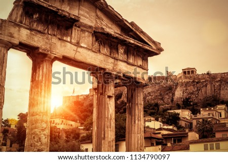 Roman Agora at sunset in summer, Athens, Greece. It is one of the main landmarks of Athens. Famous Acropolis in the distance. Scenery of sunny Ancient Greek ruins in Athens centre in sun light.