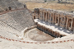 Roman amphitheater in the ruins of Hierapolis. Panoramic view of antique theater in ancient greek city Hierapolis. The ancient theater. The ruins of the ancient city at Pamukkale, Turkey.