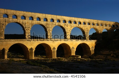 Roman aqueduct Pont du Gard in France illuminated at night