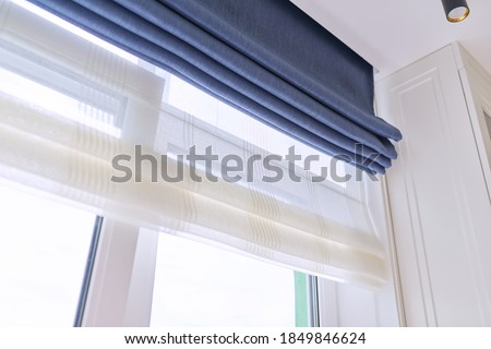 Roman blind in the interior detail close-up. Curtain blue blackout fabric, sheers white linen, fashionable modern window decoration design at home Сток-фото ©