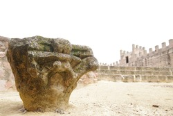 Roman capital abandoned on the floor with a background with an staircase and the walls of a castle with merlons.
