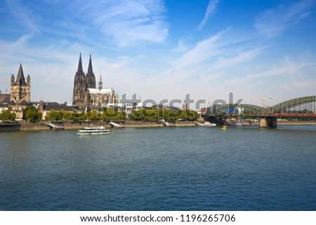 Roman Catholic Gothic Cathedral, Great St. Martin church, main train station and  Hohenzollern Bridge in Germany, view from the other side of Rhine river.