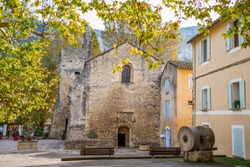 Roman church of Saint-Veran, village Fontaine-de-Vaucluse, Provence, France. Sculpture The Vanquished Coulubre in front of the church.