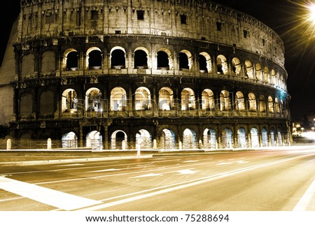 Roman Coliseum by night with some traffic