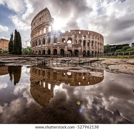 Roman Colosseum in Rome Italy with a reflection on water with the sun shining through the clouds