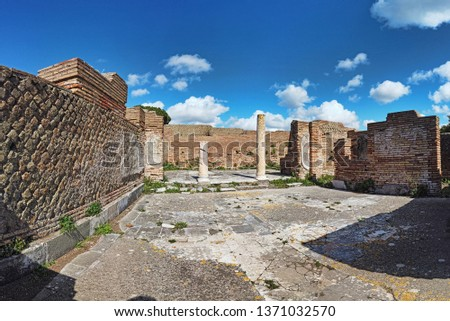 Roman empire panorama at archaeological excavations of Ostia Antica beautiful architecture with columns and remains of pavement , brick walls