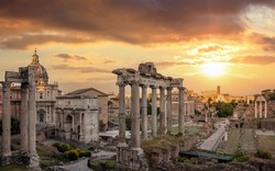 Roman Forum at sunset in Rome, Italy. Roma top landmark and tourists attraction. Ruins of the ancient forum at Palatino hill, Scenic urban landscape in the evening, cloudy sky.