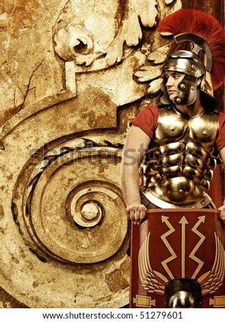 Roman legionary soldier in front of abstract wall - stock photo