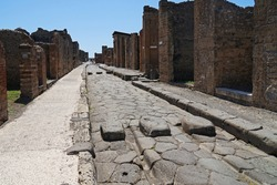 Roman paved road with stepping stones for safe pedestrian crossing, Pompeii famous ancient city archaeological site near Mount Vesuv, popular tourist guided tour destination, Pompei, Italy