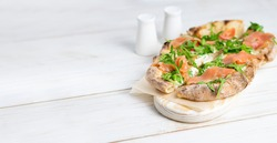 Roman pizza with salmon cut in pieces and served on a white wooden board. Traditional roman pizza with fish